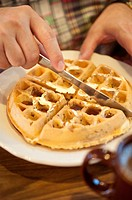 Close up view of a man cutting a breakfast waffle with a knife in a restaurant.
