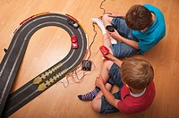 A  picture of two boys  6 &amp; 10  playing with a Hornby Scalextric racing car set game in the Uk