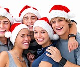 Closeup portrait of young smiling friends wearing Christmas hats