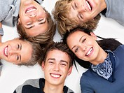 Closeup of happy young friends smiling and lying on white floor