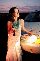 26 year old brunette woman wearing a white dress on a country road holding a beer bottle at dusk