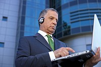 Mature man with headset using a laptop