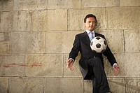 Businessman playing with a soccer ball