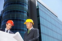 Two Businessman with hardhats watching a plan (thumbnail)