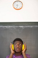 Student wearing ear protection leaning against blackboard