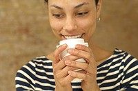 Smiling young woman holding plastic cup