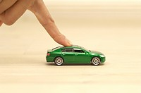 Finger pushing green toy car