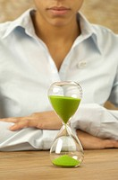Woman looking at hourglass with green sand