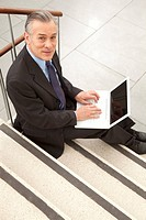 Businessman using laptop on stairs, Munich, Bavaria, Germany