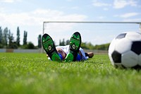 Exhausted kicker lying on grass
