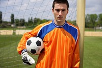 Goalkeeper holding ball leaning against goal, portrait