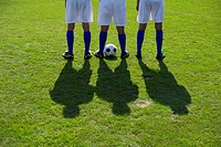 Three soccer players standing side by side