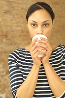 Serious young woman holding plastic cup