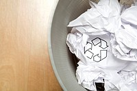 Crumpled paper in wastepaper basket with recycling symbol, Germany