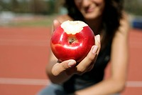 Woman holding an apple at camera
