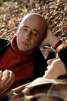 Mature couple lying on leaves and talking