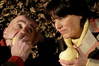 Mature couple lying on leaves and eating pears