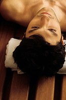Darkhaired Man with a Towel under his Head _ Bench _ Sauna _ Relaxation _ Wellness
