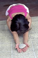 Darkhaired Woman bending over her knees holding a Stone in her Hands _ Praying Position _ Yoga _ Posture