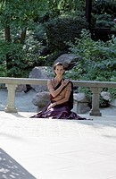 Darkhaired Woman in a Saree sits kneeling on a Terrace _ Meditation _ Tradition