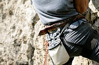 Young man with a harness and a chalk bag is climbing up a rocky wall part of, close_up