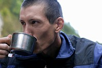 Young man with a shaved head is drinking from a metallic cup, close_up