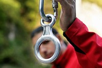 Young man with black hair is holding up a carabiner with a belay device part of, selective focus