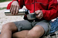 Man sitting outside while having a tee out of a thermos flask