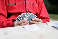 Man in a red jacket is playing cards part of, selective focus