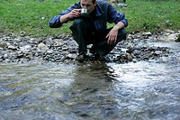Young man is drinking water from a rivulet part of