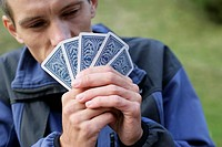 Young man is holding cards in front of his face part of, close_up
