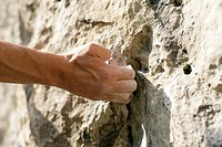 Dirty male hand touching a rocky wall, close_up, selective focus