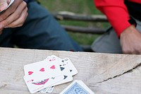 Two men playing cards on a wooden table outdoors part of, selective focus