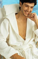Darkhaired Man in a Bathrobe sits on a Canvas Chair laughing _ Baths _ Leisure Time _ Wellness