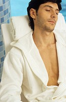 Darkhaired Man in a Bathrobe sits on a Canvas Chair snoozing _ Baths _ Leisure Time _ Wellness