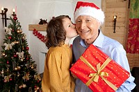 Girl passing Christmas present to grandfather
