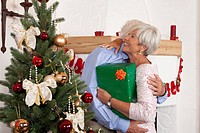 Couple with present embracing at Christmas tree