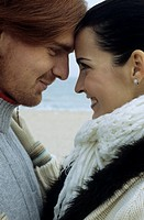 Young brownhaired Woman and auburn_haired Man touching their Foreheads _ Love _ Togetherness _ Beach