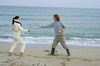 Young Couple fighting with little Sticks - Imitation of a Swordplay - Fun - Leisure Time - Beach (thumbnail)