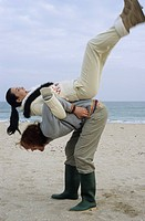 Longhaired Man pulling his Girlfriend onto his Back _ Fun _ Physicalness _ Relationship _ Beach