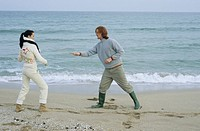 Young Couple fighting with little Sticks _ Imitation of a Swordplay _ Fun _ Leisure Time _ Beach