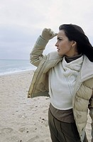 Young brownhaired Woman watching out for something _ Winterly Clothing _ Season _ Beach