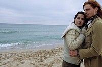 Young auburn-haired Man holding a brownhaired young Woman in his Arms - Love - Togetherness - Beach (thumbnail)