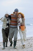 Two young Women with a Man between them strolling along the Beach _ Friendship _ Trip _ Season