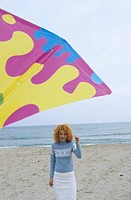 Young Woman with red Curls holding a Kite on a String _ Leisure Time _ Fun _ Beach _ Season
