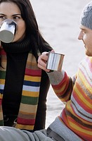 Young Couple drinking from metallic Cups _ Gesture _ Hot Beverage _ Season _ Beach