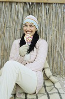 Darkhaired young Woman with a crocheted Hat holding a Lollipop _ Sweets _ Season