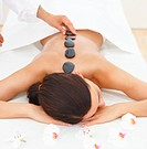 Woman receiving hotstone massage at spa and wellness center