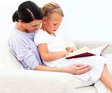 Mother and daughter sitting on couch and reading book at home