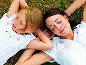Closeup of young mother with her daughter resting on grass